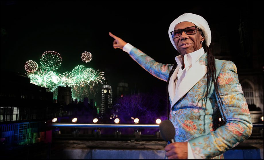 Nile Rodgers with mic on CHW balcony during NYE fireworks