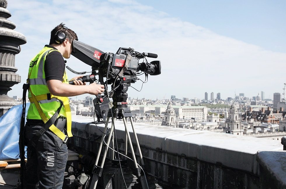 Member of film crew looking into camera over Central Hall Westminster balcony