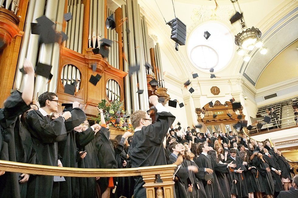 Graduates in robes throwing hats into air at graduation ceremony