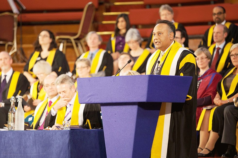 Robed academic speaking at lectern during graduation ceremony