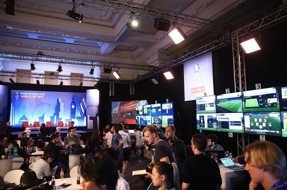 Attendees at live interactive FIFA event, facing screens & FIFA display