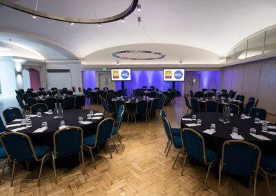 Aldergate room in cabaret set-up with purple uplighters