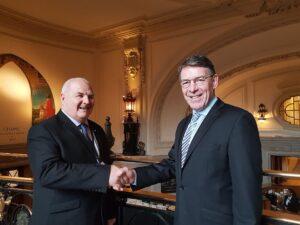 Two men shaking hands inside Central Hall Westminster