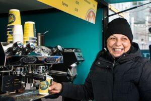 Women making coffee in Change Please coffee van